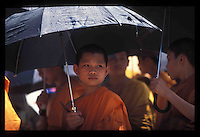 The Lao New Year in the middle of April is a time for celebration and reflection. Water is used for cleansing and offered liberally to one and all.  Umbrellas are used more for shade than keeping dry. Pentax Spotmatic film camera. 2004