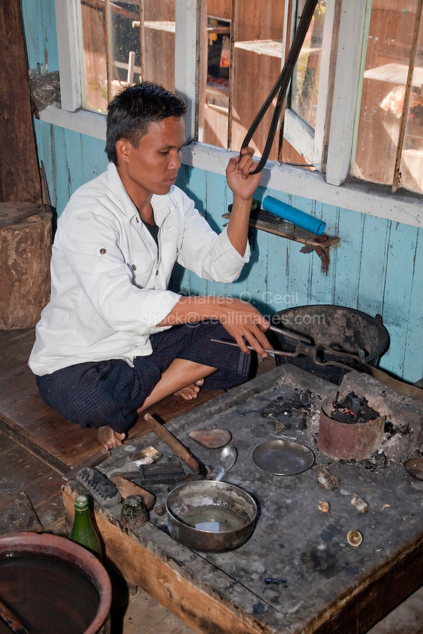 Myanmar, Burma.  Young Man Working with Silver to Make Jewelry, Inle Lake, Shan State.