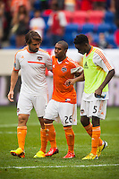 Corey Ashe (26) of the Houston Dynamo is helped off the field after the game by Mike Chabala (6) and Warren Creavalle (5). The New York Red Bulls defeated the Houston Dynamo 2-0 during a Major League Soccer (MLS) match at Red Bull Arena in Harrison, NJ, on June 30, 2013.