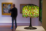 Roslyn, New York, U.S. - April 12, 2014 - During International Slow Art Day, visitors view a Tiffany Studios stained glass table lamp, Chanson de printemps after Bouguereau, and other artwork in the Garden Party exhibit at the Nassau County Museum of Art on Long Island. During this annual worldwide event, those participating went to local museums and viewed a small number of works of art, each for at least 10 minutes, and then discussed them afterward.