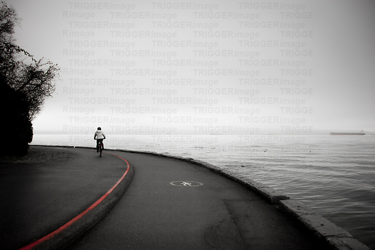 Distant figure on bicycle riding along road beside ocean shore with large tanker