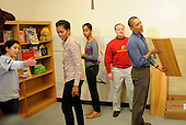 United States President Barack Obama (R) inspects a shelf as he and first lady Michelle Obama (2nd,L) and daughter Malia (C) join volunteers in a library as they participate in a service project, at Browne Education Center, in Washington, DC, USA, on the Martin Luther King Jr national holiday, 16 January 2012. The project was in memory of the legacy of community service, promoted by the late civil rights leader, who was assassinated in 1968..Credit: Mike Theiler / Pool via CNP