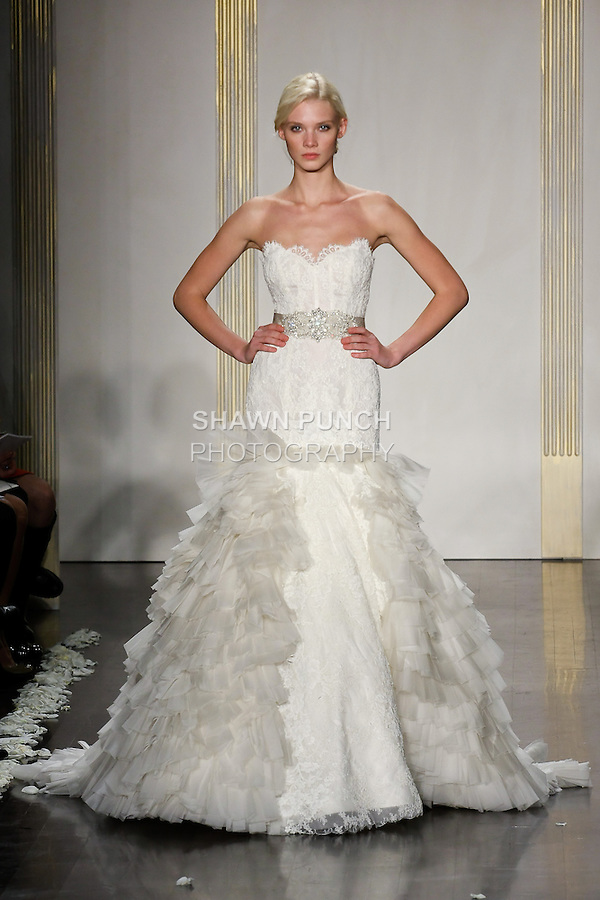 Model walks runway in an ivory alencon lace pleated net Rococo inspired gown, strapless sweetheart neckline, sheer corseted alencon lace elongated bodice, silver moire jeweled ribbon belt at natural waist, circular alencon lace skirt with ruffle pleated net godets, chapel train wedding dress by Lazaro Perez, from the Lazaro Spring 2012 Bridal fashion show.