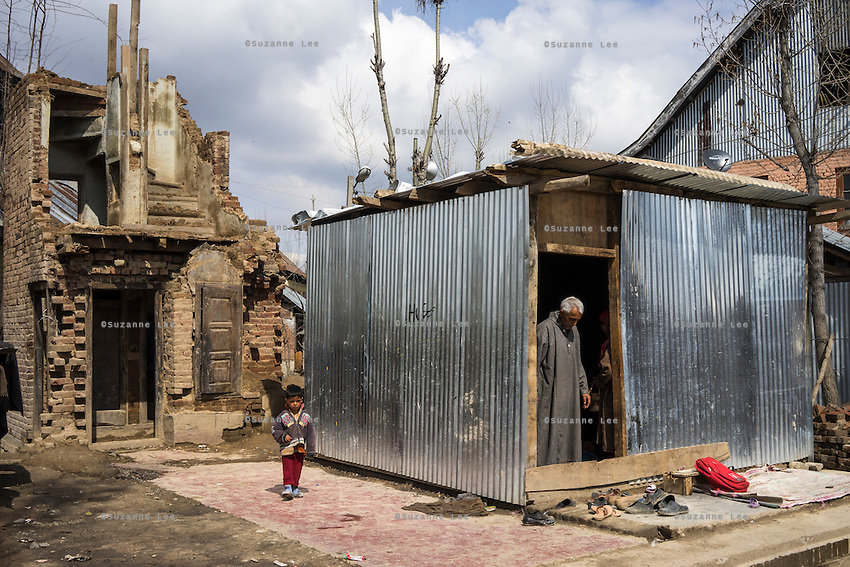 (Alison Griffin to fill in names) (Name)'s youngest son walks to his temporary shelter from the skeleton of his three storied house that was severely damaged during the floods in September in Abikarpora village on the Dal Lake, Srinagar, Jammu and Kashmir, India, as seen here on 25th March 2015. Since the flood, she has been widowed, and is left with four young children and no home. Her family now lives in a temporary shelter built using the emergency shelter kit, and continues their recovery with the help of relief kits such as education kit, food basket, hygiene kit and non-food items from Save the Children. Photo by Suzanne Lee for Save the Children