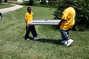 Two students from Dillard Academy Charter School carry a keyboard after performing for over 100 teenagers attending the Rooted In Community Conference, Goldsboro, N.C., July 24, 2010