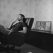 "Simione, in his ""office"", sitting smoking at his desk. Even though he has an office with expensive furniture he still prefers to conduct his business outside on the bonnet of a car. Sintesti, Romania,  September 2004.."