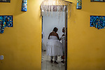 RIO DE JANEIRO, BRAZIL - JANUARY 24: A woman overcome by an orixa is led into a private room to release the spirit, during a candomble ceremony, in Rio de Janeiro, Brazil, on Saturday, Jan. 23, 2015. Brazil's Afro-Brazilian religions which in recent years have come under increasing threats and prejudice, particularly from the growing number of evangelical churches. Candombl&eacute; originated in Salvador, Bahia at the beginning of the 19th century when enslaved Africans brought their beliefs with them. Umbanda and candombl&eacute; are Afro-Brazilian religions practiced in mostly Brazil. <br /> (Lianne Milton for the Washington Post)