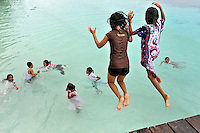 Children playing in the ocean at popular Hunimua Beach on the northern, mainly Muslim part of Ambon Island. The 1999-2002 religious war between Maluku's Christian and Muslim populations, mainly centred on Ambon Island, led to over 5000 deaths and to around 500,000 people become displaced. Destroyed homes and offices, churches and mosques are slowly being either torn-down or renovated.  Urban centres, such as Ambon City, continue to be split along largely sectarian lines, and tensions are never far below the surface. Riots between Christian and Muslim youths erupted in September 2011 and, most recently, June 2012, though luckily simmered down just as quickly, partly due to community leaders learning how to defuse tensions from the earlier, more devastating, conflagration. /Felix Features