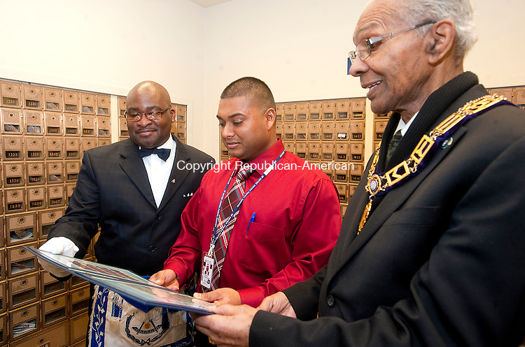 WATERBURY, CT FEBRUARY 11, 2014_ 020714JS04-Norman L. Andrews, Jr., Grand District Lecture of CT, left, Vickram Shamchander, Customer Service Manager at the Waterbury Main Post Office and Rev. Thomas Mallory, Chaplain Emeritus for Prince Hall Mason, right, look over the Post Office's stamps for Black History Month Tuesday at the post office main branch in Waterbury. Being honored this year is Shirley Chisholm (1924-2005) , the first black woman ever elected to Congress and the 1963 March on Washington. <br /> Jim Shannon Republican-American