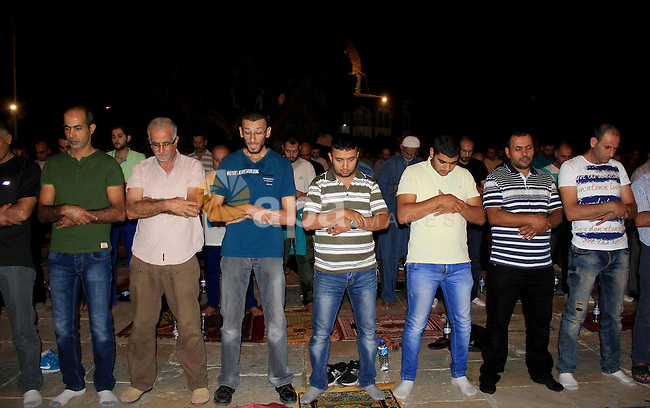 """Palestinian Muslim worshippers perform """"Taraweeh"""", nightly prayer of the month of Ramadan, in front of the Dome of the Rock mosque, in Jerusalem's old city on June 25, 2016. Ramadan is sacred to Muslims because it is during that month that tradition says the Koran was revealed to the Prophet Mohammed. The fast is one of the five main religious obligations under Islam. More than 1.5 billion Muslims around the world will mark the month, during which believers abstain from eating, drinking, smoking and having sex from dawn until sunset. Photo by Mahfouz Abu Turk"""