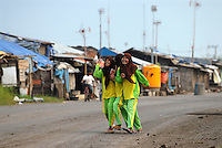 Schoolgirls on the former highway that now houses their makeshift Internally Displaced Persons (IDP) camp in Besuki. Since May 2006, more than 10,000 people in the Porong subdistrict of Sidoarjo have been displaced by hot mud flowing from a natural gas well that was being drilled by the oil company Lapindo Brantas. The torrent of mud - up to 125,000 cubic metres per day - continued to flow three years later.