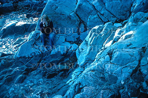 Girl sitting along rocky shore.