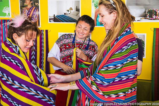 The 2015 Santa Fe International Folk Art Marketl, featuring scores of artists from a large number of countries,  has become the most popular summer event in a city already filled with a number of famous, world class cultural celebrations.Volunteer Julianne Parkinson helps Guatamalan artist Lina Barrios to display her weavings to customers.