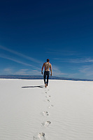 back of a shirtless man walking on a sand dune in White Sands National Park