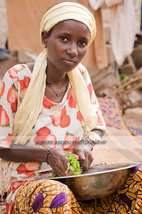 In Ouagadougou, Burkina Faso, a young Fulani woman prepares dinner for the family.  In this small West African country, where the majority of the population lives on less than a dollar a day, the struggle for food is a daily burden.