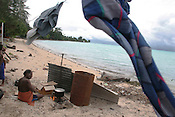 A elderly man prepares hot water on a fire on the beach, on the island of Kiribati in the South Pacific. The islands, and their way of life, is endangered by rising sea water levels which are eroding the fragile atoll, home to approximately 92,000 people.