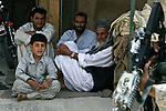 Three men and a boy watch U.S. soldiers and Afghan police on patrol in the Maiwand district bazaar in Kandahar province, Afghanistan. Aug. 8, 2008. DREW BROWN/STARS AND STRIPES