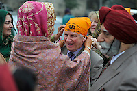 Before the wedding ceremony of British/Punjabi couple Lindsay and Navneet Singh, the father of the bride has his headscarf put on.