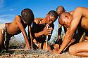 Botswana, Kalahari, bushmen (san) making fire the traditional way by rapidly turning wooden stick