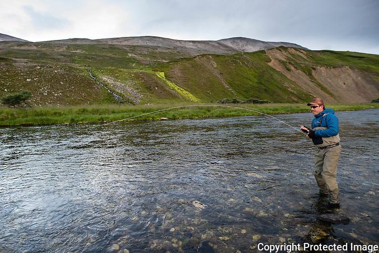 Mann kjører smålaks på fluestang i øvre del av Komagelva. ---- Man fighting small salmon i Komagelva.
