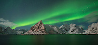 Aurora Borealis - Northern Lights fill sky over Olstind mountain peak and reflect in fjord, Toppøya, Lofoten Islands, Norway