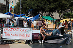 People enjoying afternoon sun at the antigovernment protest camp at Placa de Catalunya, Barcelona, Spain. Banner reads: Artkatraz takes to the streets&quot;. The square has been relatively quiet since police attacked and beat protestors on May 27 2011.