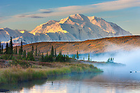 Morning fog over the calm waters of Wonder lake at sunrise, Mt McKinley looms in the distance, Denali National park, Alaska.