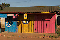 Shipping containers make instant architecture for lock-up storage across Africa. Mobile operator brands identify by colour - Uganda Telecom, MTN, Zain. Operators supply paint and logos for those reselling their vouchers. It's becoming hard in some areas to find a painted structure that is not one of these colours. Along with the Orange Orange, and the red-and white of Warid, this colour scheme is almost an unofficial national flag of Uganda.