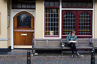 In Utrecht zit een jonge vrouw op een bankje voor een gesloten cafe aantekeningen te maken.<br /> <br /> In Utrecht a young woman is writing notes, sitting on a bench in front of a closed cafe.