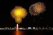 Fireworks display over a river at Kuwana City, Japan.
