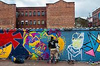 A Colombian graffiti artist named Stinkfish sprays graffiti on the wall in La Candelaria, Bogota, 10 July 2010.