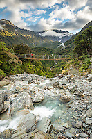 Wild Tekano Creek with trampers on swingbridge near Douglas Rock Hut in Copland Valley at sunrise, Westland National Park, West Coast, South Westland, World Heritage Area, New Zealand