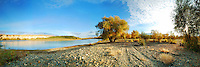 Spectacular riverside panoramic landscape scenery of Xinjiang Province surrounded by autumn trees in golden yellow color setting. Breathtaking China nature fine art photography by Paul Chong.