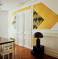 Graphic patterns, added to a simple palette of white, black and gold create an elegant combination, whilst the contemporary furniture contrasts with the original period features in this Paris apartment. The dining room is spacious and minimal with simple furniture