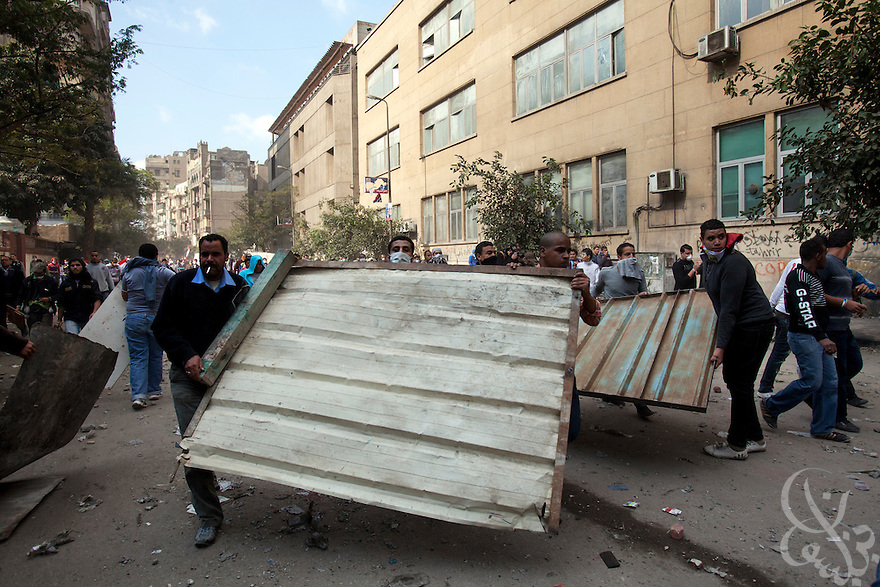 Egyptian protestors try to build makeshift barricades during street battles with security forces  November 21, 2011 near Tahrir square  in central Cairo, Egypt. Thousands of protestors demanding the military cede power to a civilian government authority clashed with Egyptian security forces for a third straight day in Cairo, with hundreds injured and at least 24 protestors killed.  (Photo by Scott Nelson)