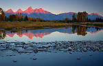 Wyoming, Teton National Park. The Teton Mountain Range with morning sun reflected in the South Fork of the Snake River in autumn.