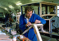 Engineer working on timber frame of vintage car being restored at Ashton Keynes Vintage Restorations in Wiltshire, UK