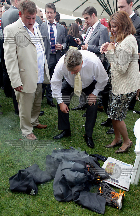 A man accidentally sets his jacket on fire in the general public area at the Royal Ascot race meeting. The annual event, during which each day begins with the Queen's arrival in a horse drawn carriage, dates back to 1711 when Queen Anne organised the first races on what was then a heath near Windsor Castle.