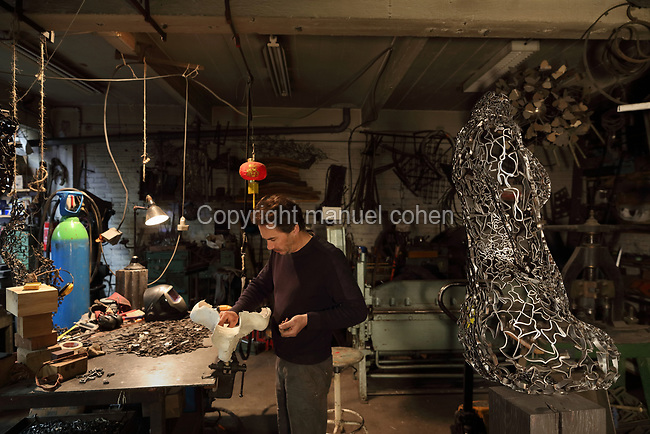 Nicolas Desbons, metalworker and artist, working on a figurative sculpture made by placing square of steel inside a plaster mould and soldering them together, in his Soleil Rouge workshop, photographed in 2017, in Montreuil, a suburb of Paris, France. On the right is a sculpture of a female torso made from cross-sections of steel tubes manipulated into organic shapes and soldered together. Desbons works mainly in steel but often in conjunction with other materials such as fibreglass, glass and clay, using both cold metal and forge techniques. He produces both figurative and abstract sculptures as well as furniture and lighting. Picture by Manuel Cohen