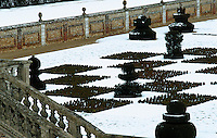 Snow covers a sunken garden designed like a chessboard with topiary hedges clipped in the shape of chess pieces