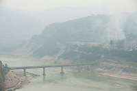 Daytime landscape view from the Sānménxiá Dam of a bridge on the Huang He and smokestacks at a power plant facility in the Sānménxiá Shì Húbīn District in Hénán Province.  © LAN