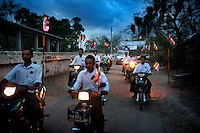 Villagers from Kyaw Min drive ahead of a vehicle carrying U Wirathu, the spiritual leader of the Buddhist nationalist 969 Movement, in a convoy as he arrives to give a sermon at the Shwe Areleain Monastery in Kyaw Min Village, Myiamu Township. U Wirathu is an abbot in the New Maesoeyin Monastery where he leads about 60 monks and has influence over more than 2,500 residing there. He travels the country giving sermons to religious and laypeople encouraging Buddhists to shun Muslim business and communities. /Felix Features