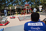 The Los Altos High School Robot, #114, is driven around a playing field towards goals setup as frisbee targets.