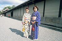 Geisha girls pause near the wall of the Imperial Palace for a photo.