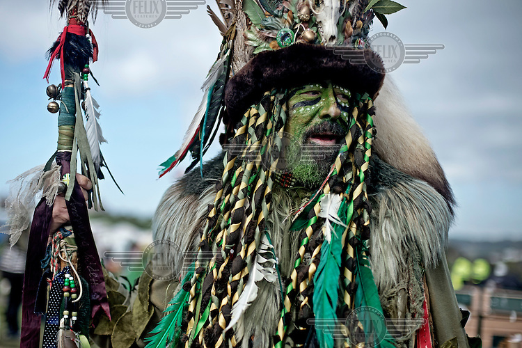 A reveller at a Jack in the Green festival. The festival is part of a recent revival of an older custom where people would wear frameworks covering much of their bodies which were decked out in foliage. The custom is connected to English May Day parades that herald  the coming of summer.