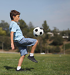 A young boy knee kicks a soccer ball in a park with copy space to right