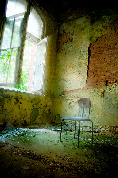 A derelict room with sunlight shining through an open window onto an old chair