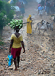 A woman carries bananas on her head as she walks down a path in the rain in Mizak, a small village in the south of Haiti.