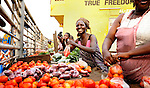 A woman selling tomatoes at the street market near the ferry in Likoni, Kenya.