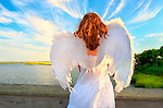 Young woman wearing angel wings spread open, seen from behind with and red hair blowing in wind. Levy Park and Preserve, Long Island, New York, USA.